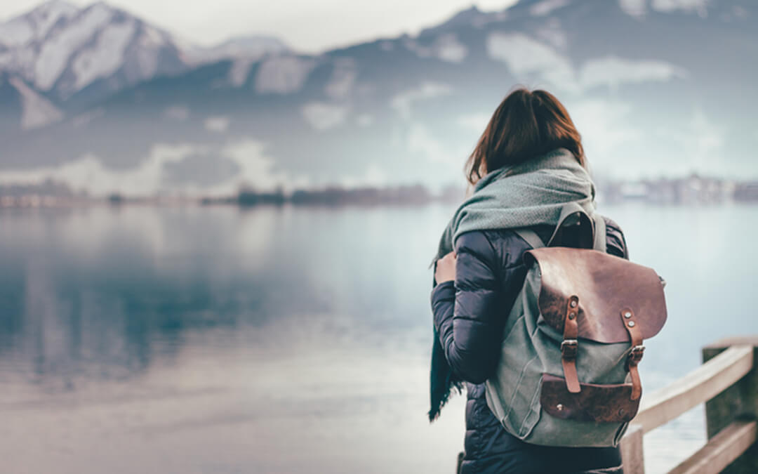 woman alone in front of lake - checklist for traveling alone if you are autistic planning