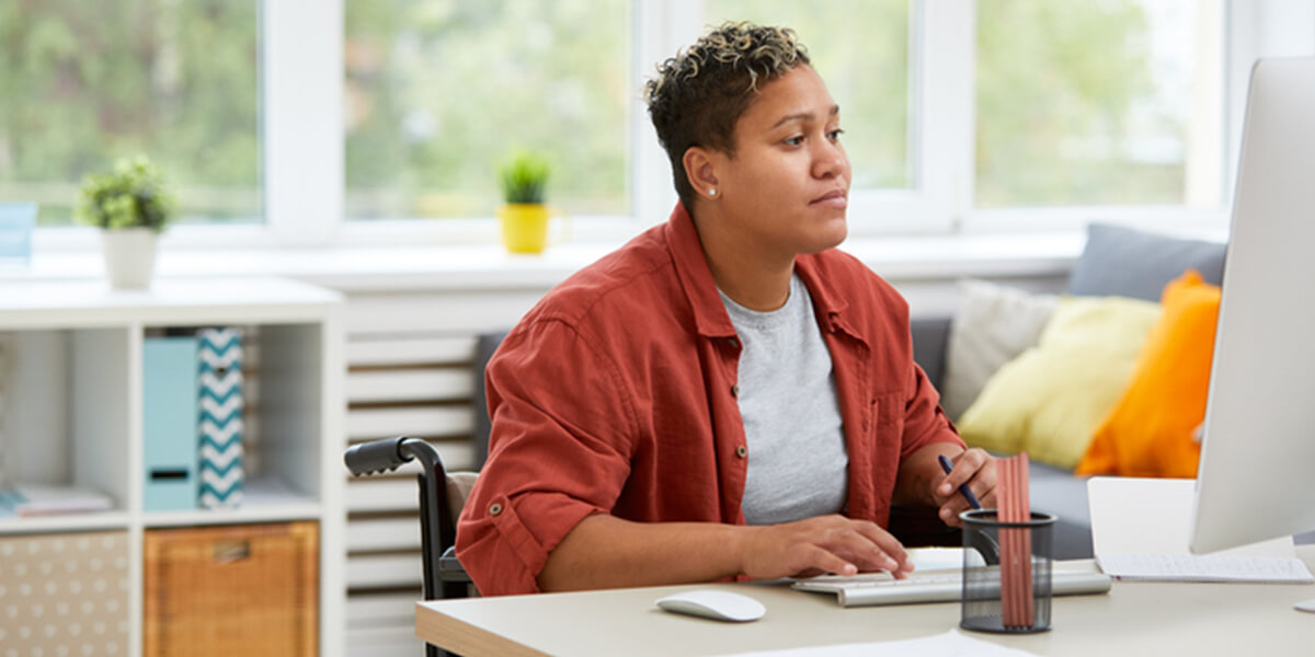 disabled woman using computer - certified neurodiverse financial planning services