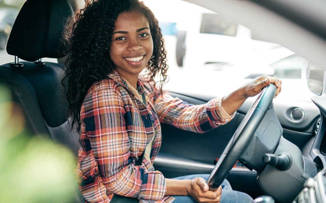millennial girl driver behind wheel of car - seven things to help autistic teens drive