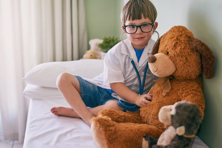 kid playing doctor with teddy bear - neurodiverse autism financial planning services farmington ct